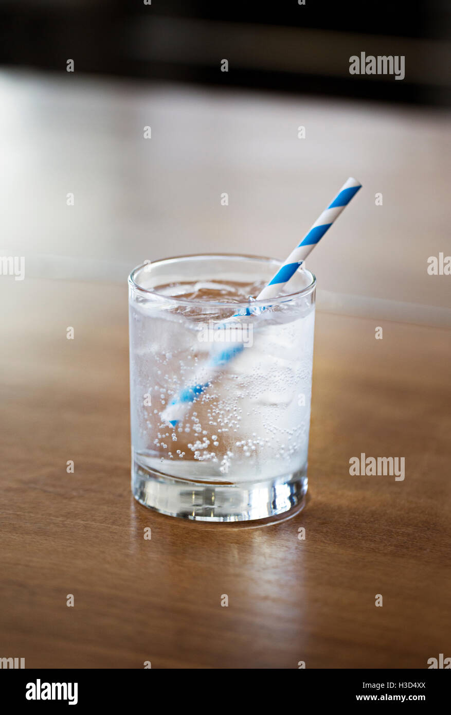 Close-up of carbonated water in glass on wooden table at home - Stock Image