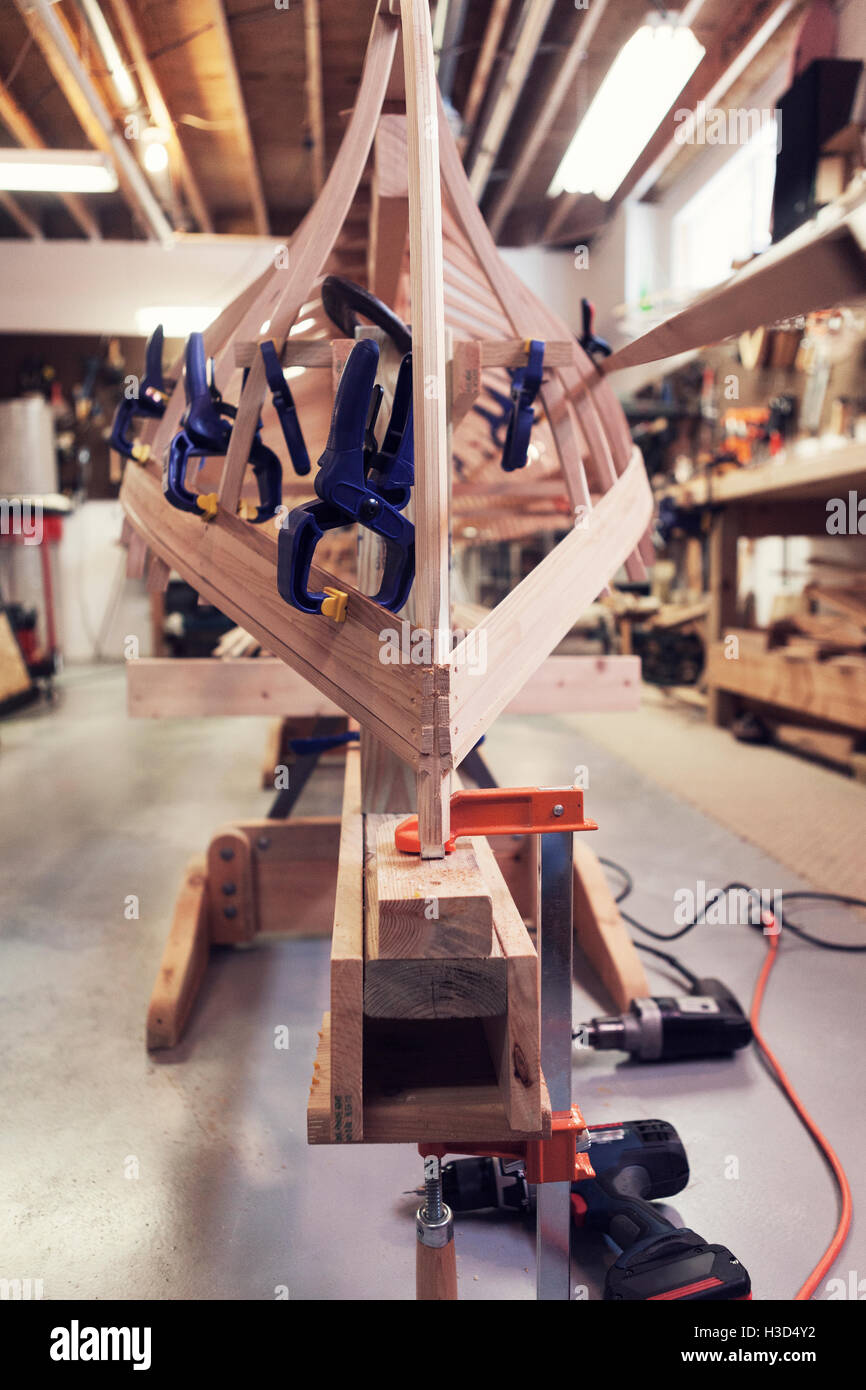 Clamps attached to incomplete wooden boat in workshop - Stock Image