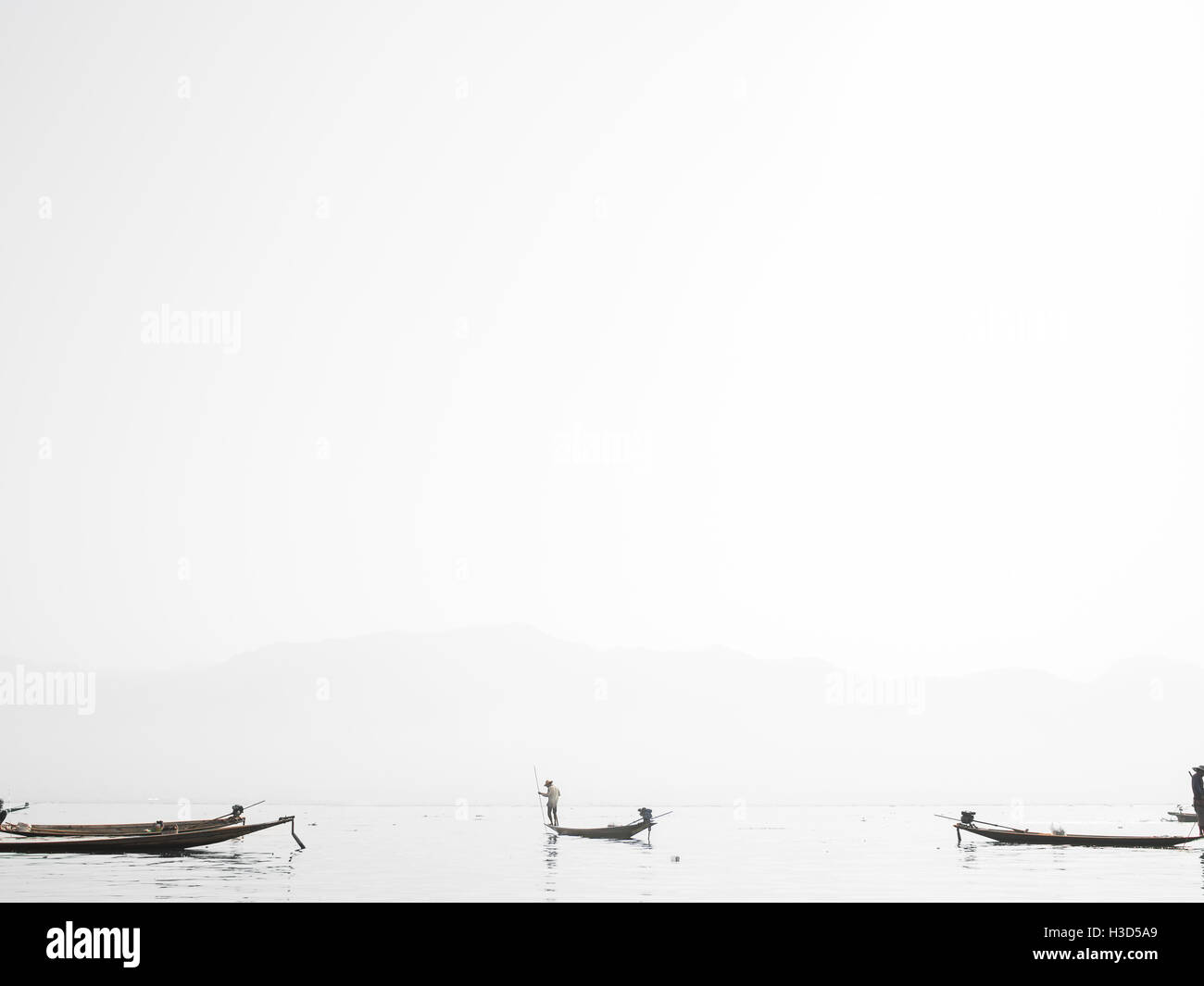 A fisherman in the middle of Inle Lake in Myanmar (Burma). The village is only accessible by boat and every structure - Stock Image