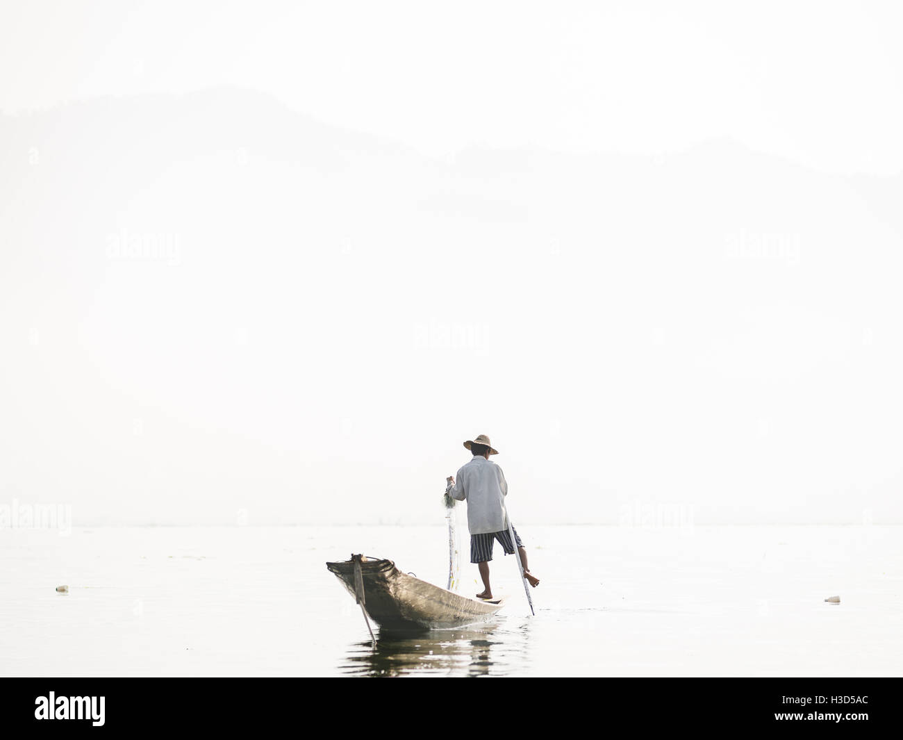 A fisherman in Inle Lake, Myanmar (Burma). They use a technique where one foot stands on the boat and the other - Stock Image