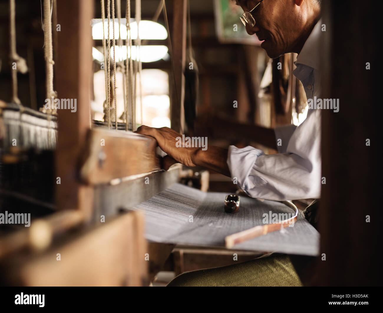 A man weaving silk in Inle Lake, Myanmar (Burma) - Stock Image