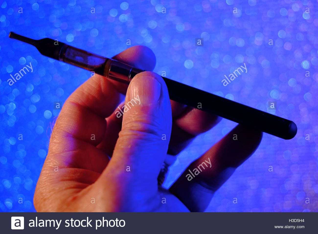 A man holds a vaporizer pen infused with medicinal marijuana. - Stock Image