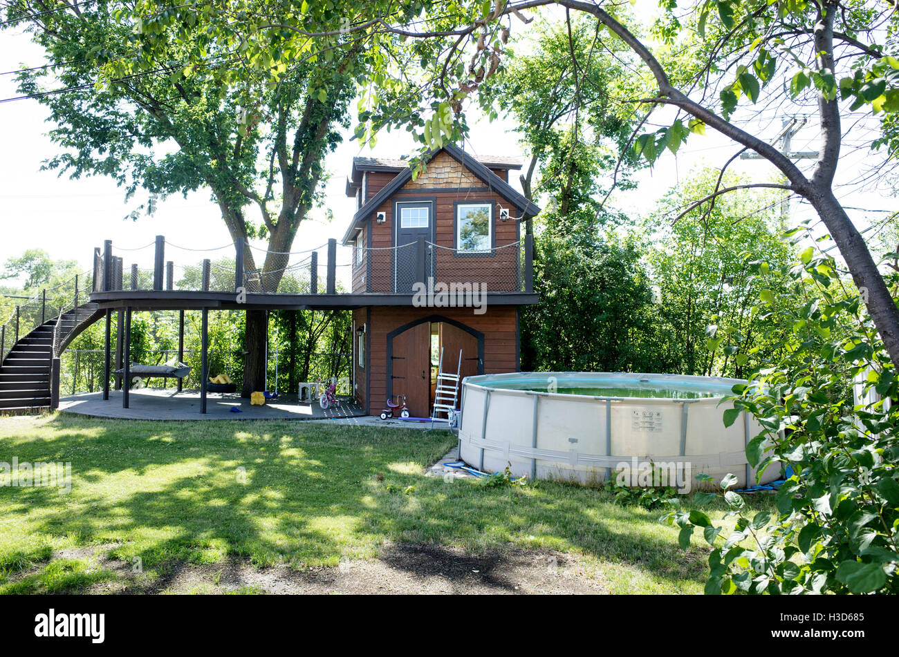 Fanciful two story tree house with a long curved stairway beside a giant hot tub.  Fergus Falls Minnesota MN USA - Stock Image