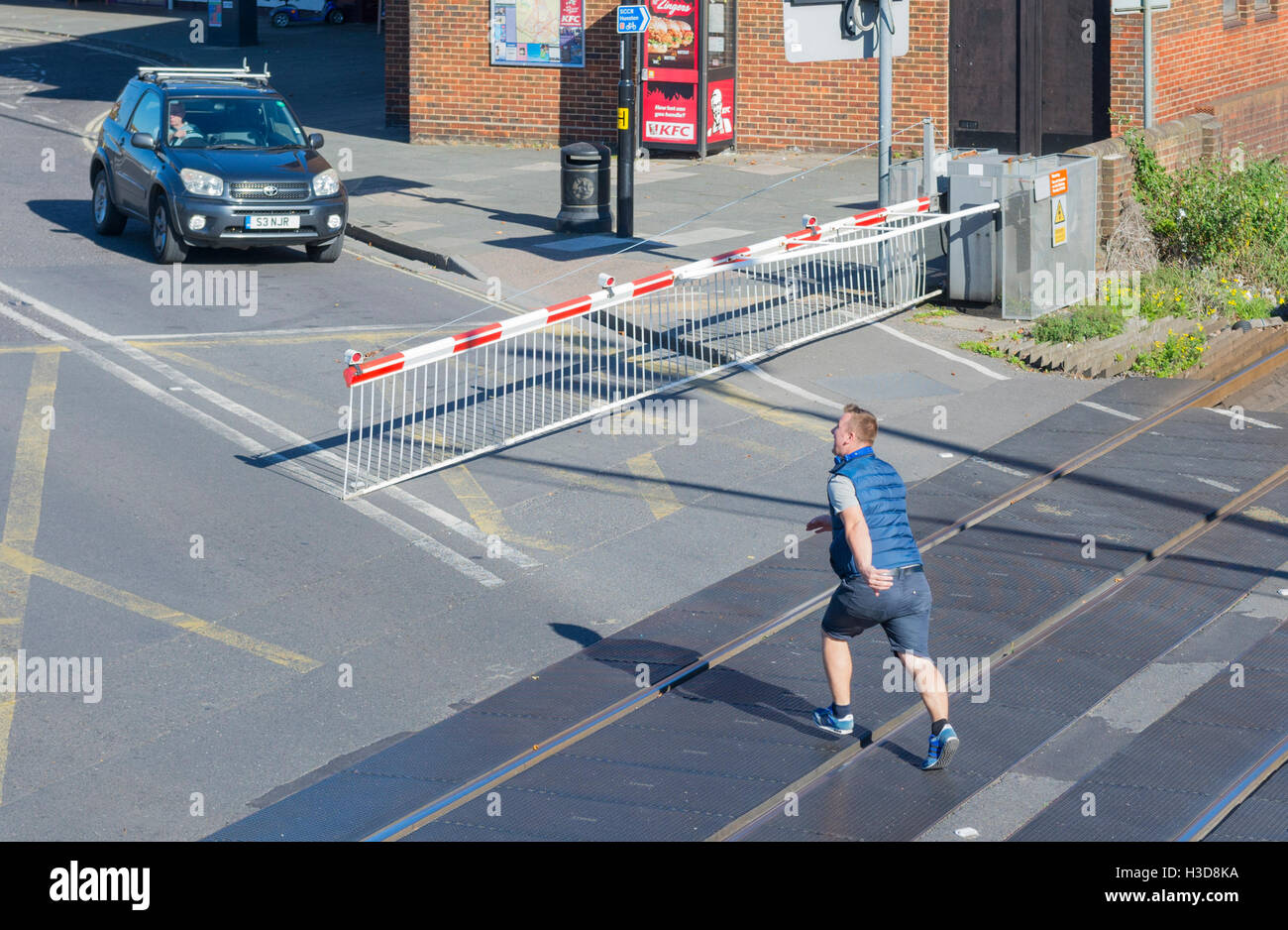Man running across railways lines at a level crossing as the gates come down. - Stock Image