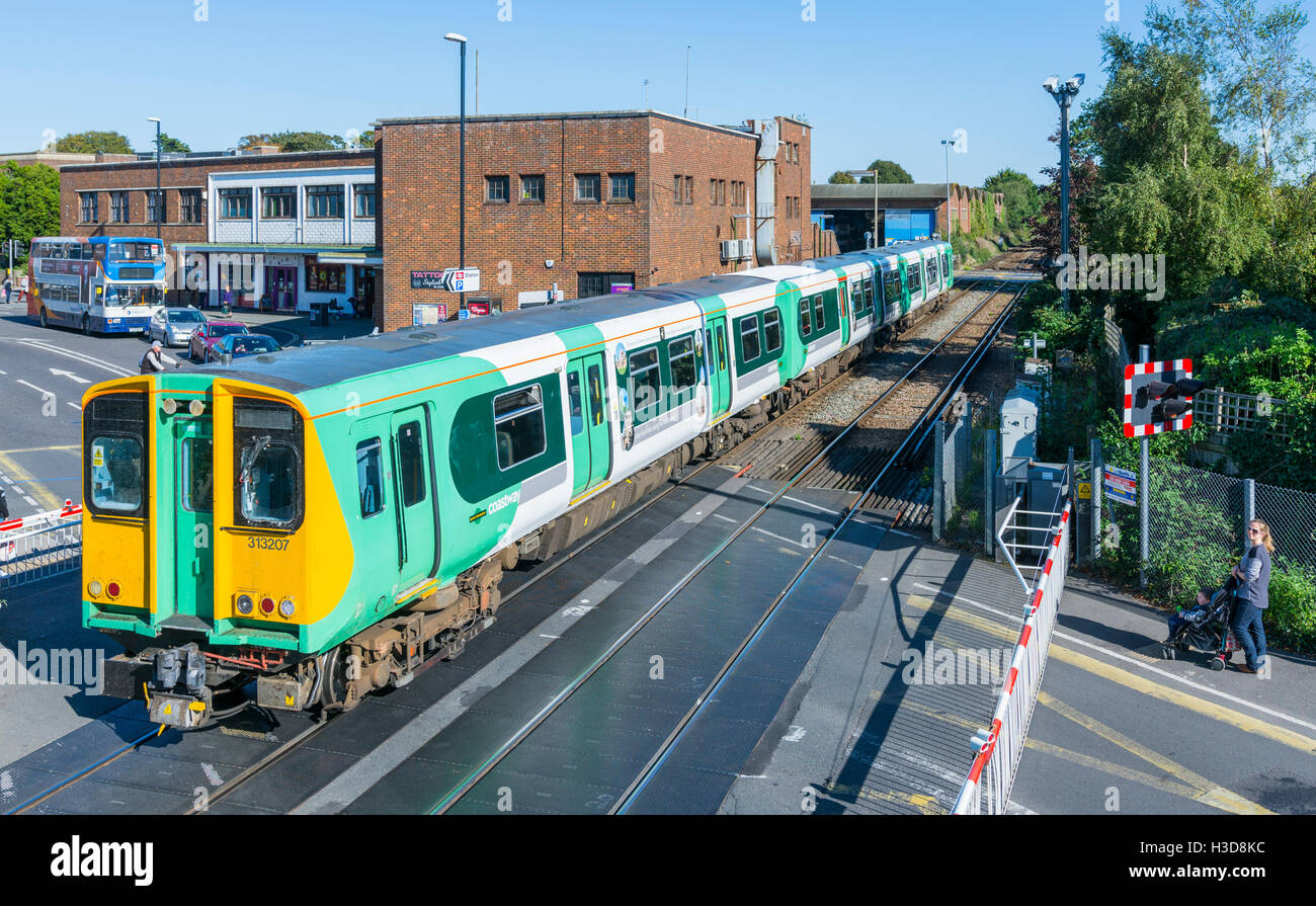 Southern Railway Coastway Class 313 train going across a level crossing in Chichester, West Sussex, England, UK. - Stock Image