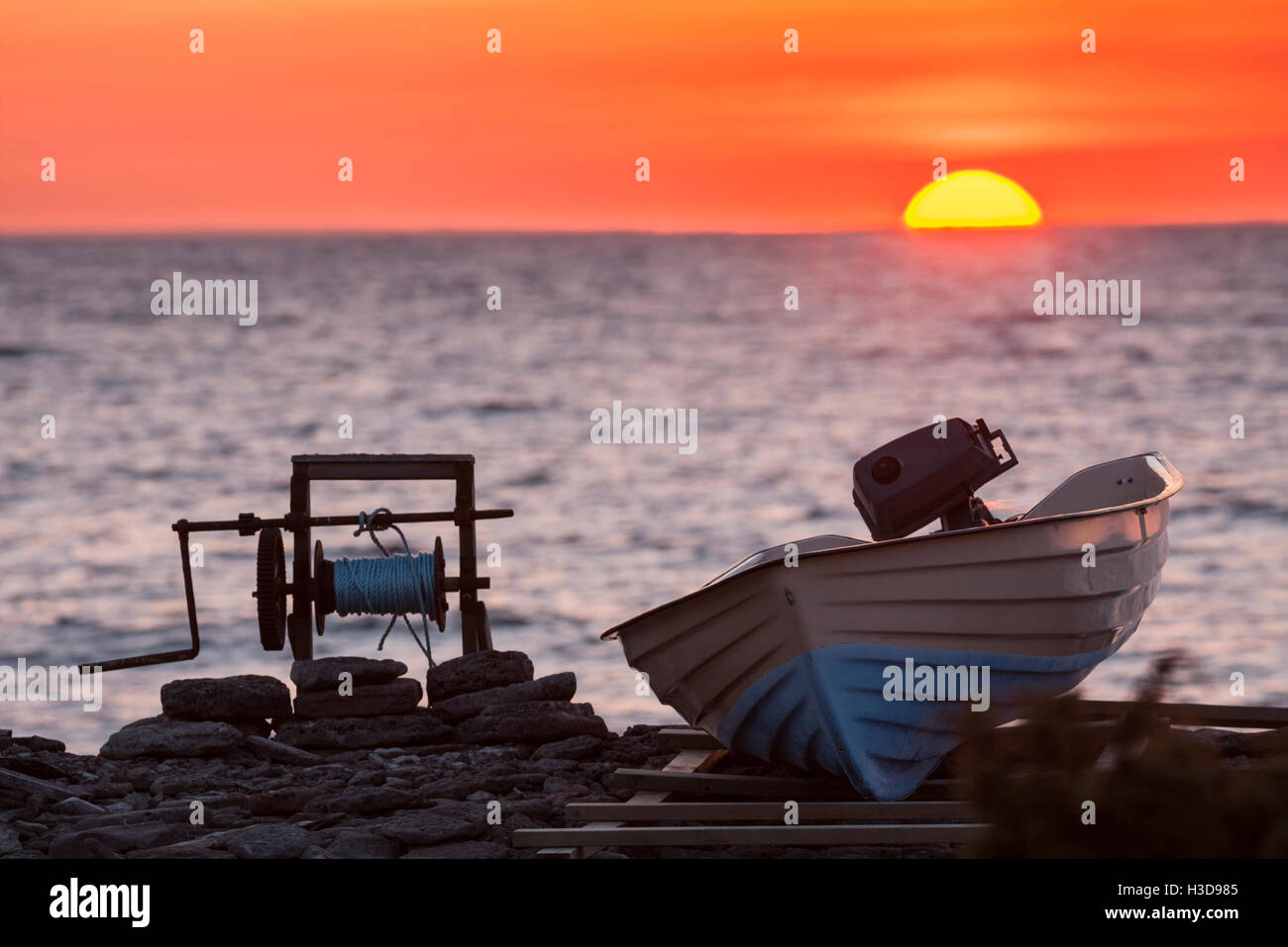 Motorboat and winch at sunset by the ocean. Sandvik. Oland / Öland, Sweden. - Stock Image