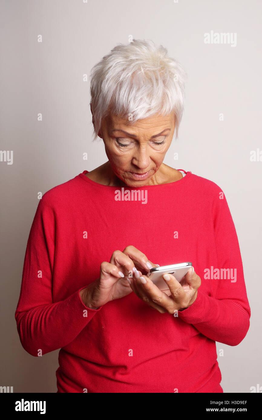 confused senior woman using smartphone - Stock Image