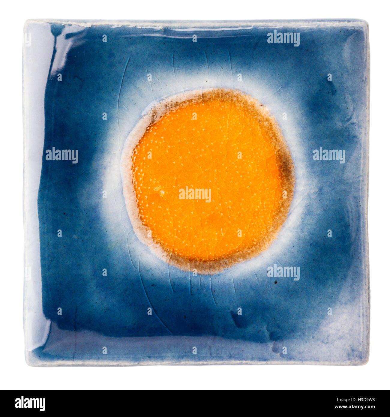 Blue handmade glazed ceramic tile with big orange dot in middle ...