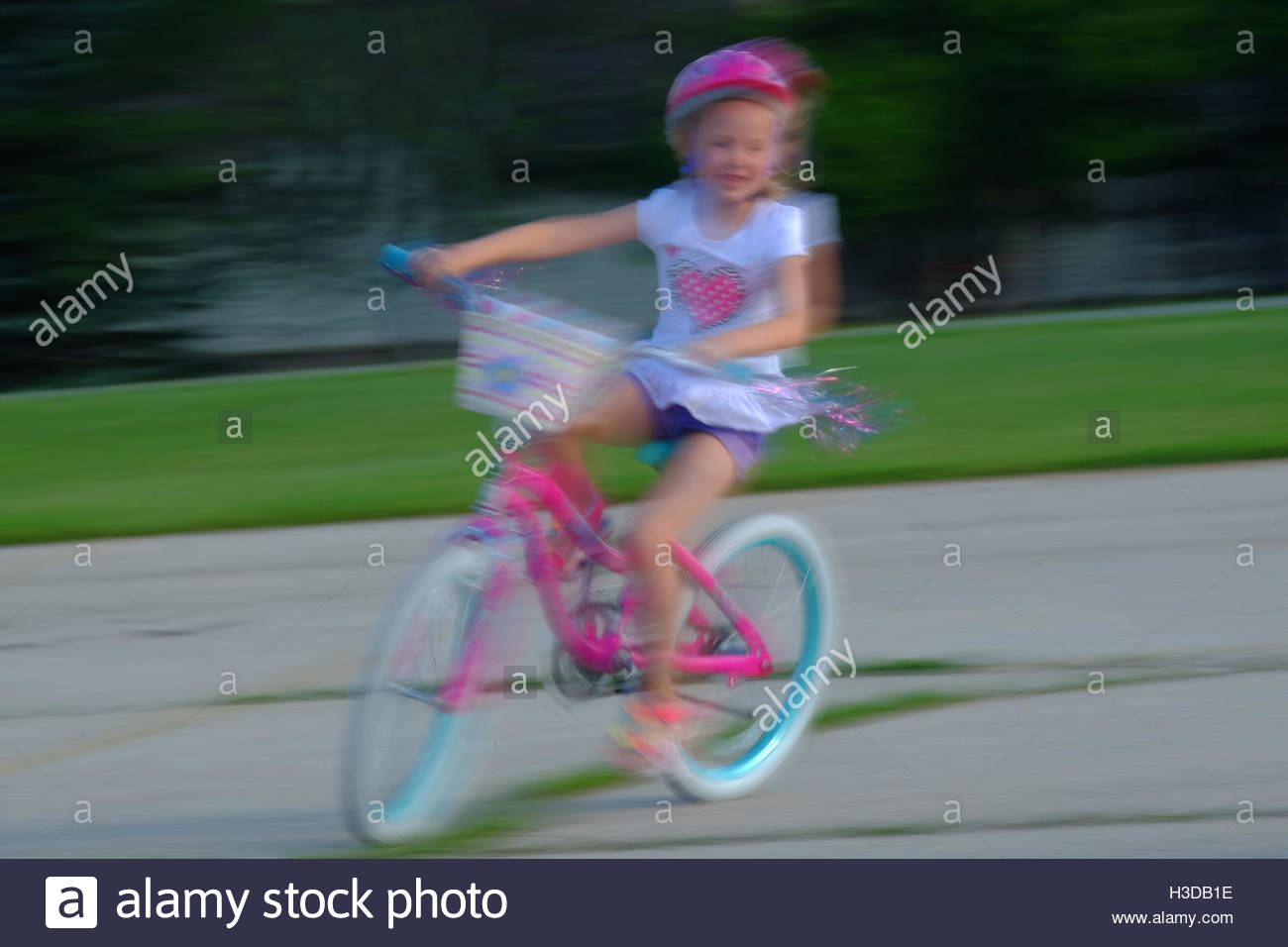 A girl practices her two wheeled bike riding skills in a parking lot. - Stock Image