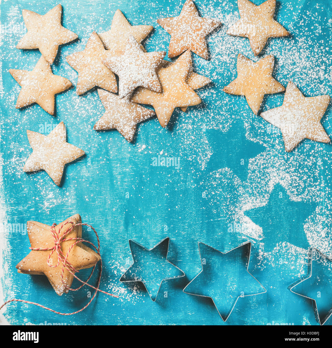 Christmas gingerbread cookies sprinkled with sugar powder on blue background - Stock Image
