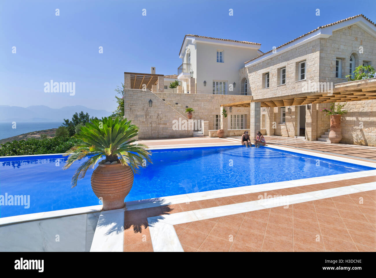 Luxury villa and exclusive private infinity pool overlooking Crete and Aegean sea with palms and typical grecian Stock Photo