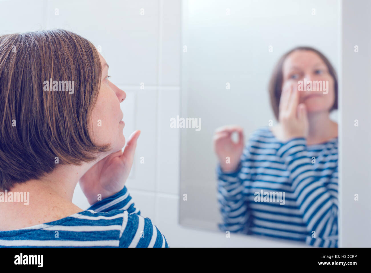 Young adult woman applying anti-aging cream in front of the bathroom mirror, selective focus - Stock Image