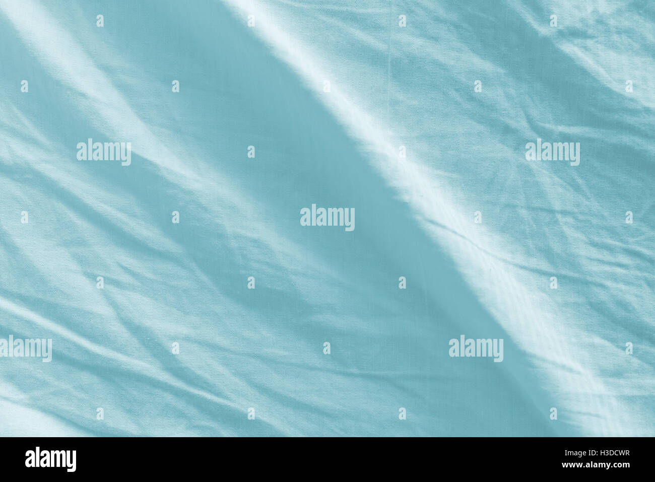 Crumpled bed sheets texture as background, top view - Stock Image