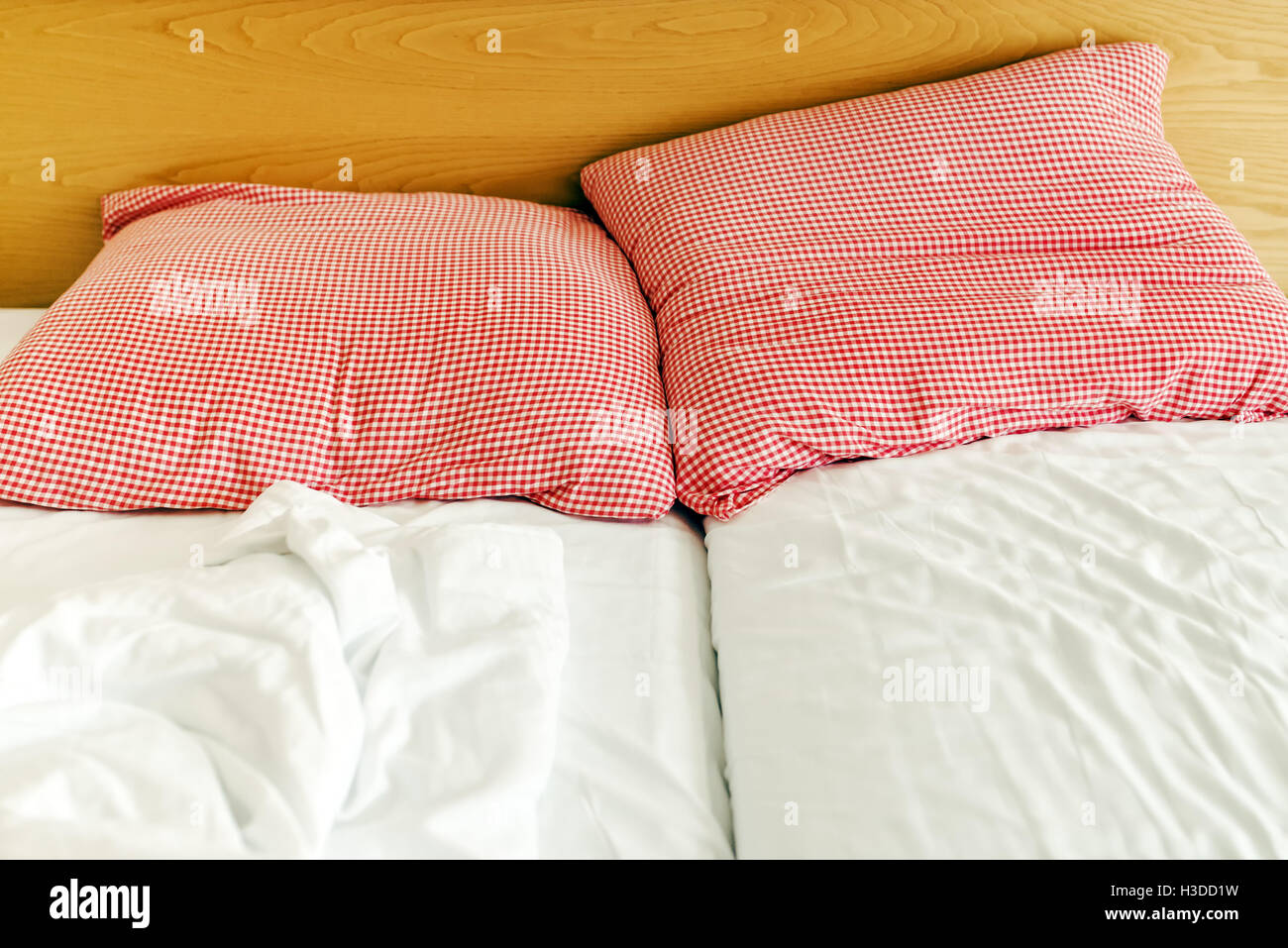 Three star hotel bed and pillows with crumpled sheets in the morning - Stock Image