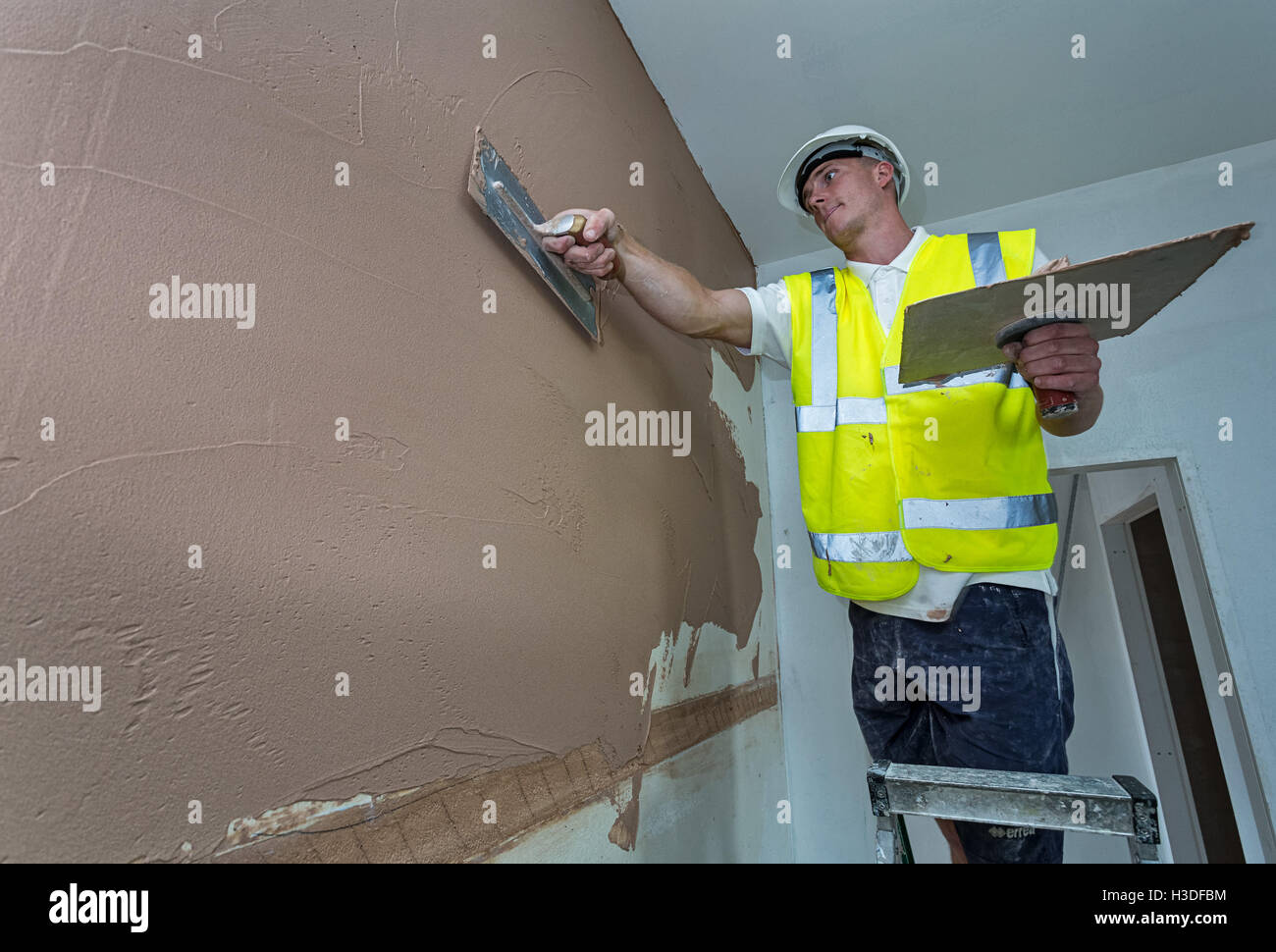 Plasterer working on a building site - Stock Image