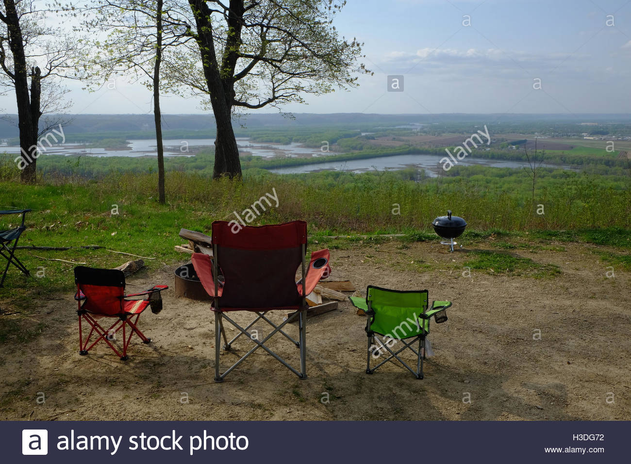 Three camp chairs near an outdoor fire pit sit at a campsite overlooking the Wisconsin River in Wisconsin. - Stock Image