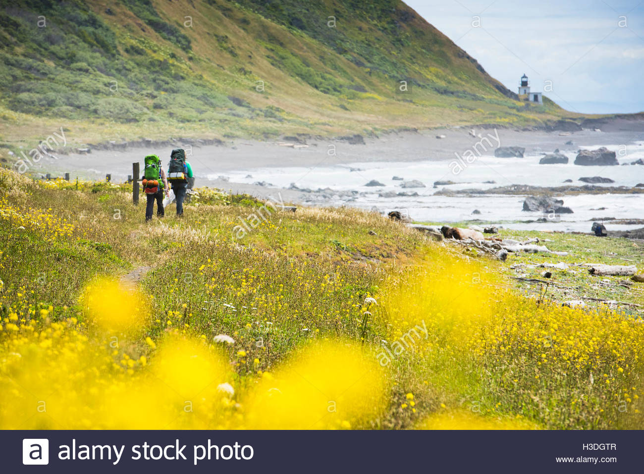 Two backpackers hiking towards a deserted light house. - Stock Image