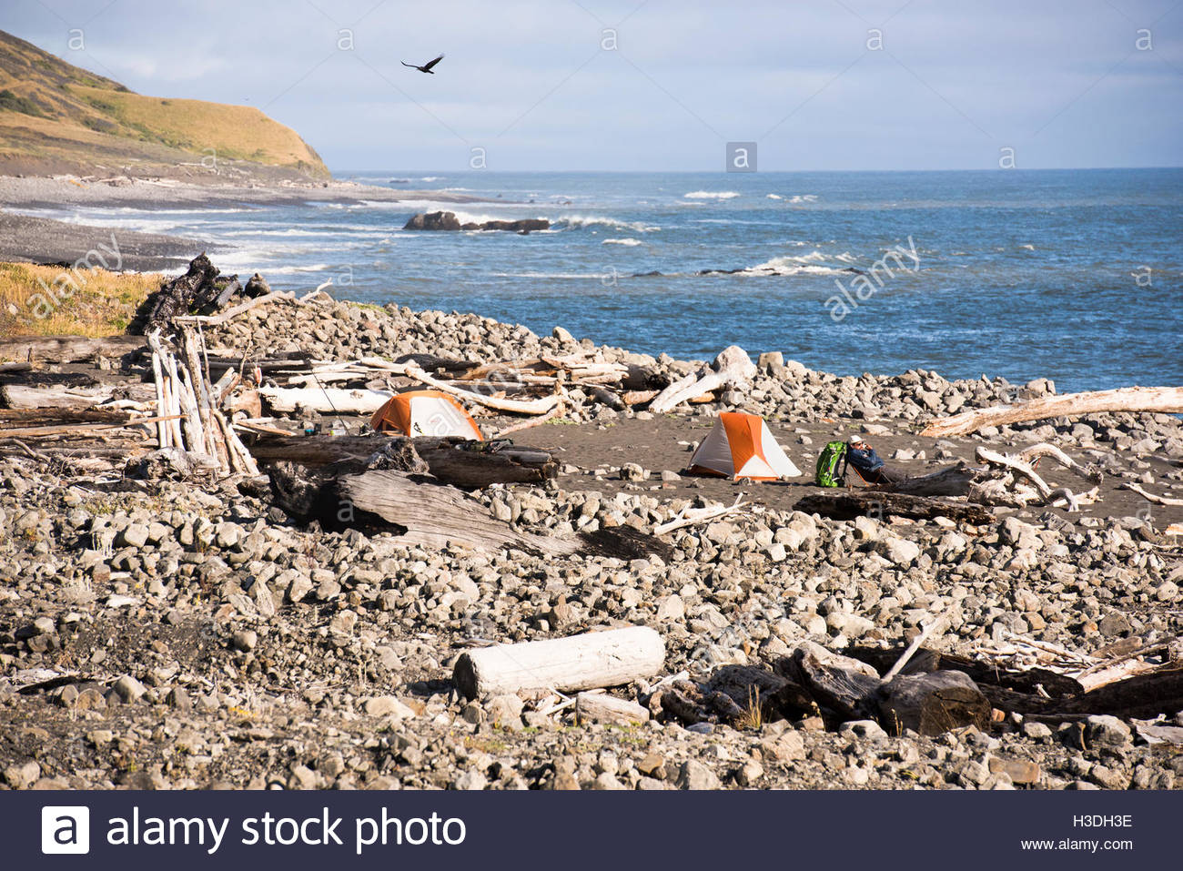 A campsite is seen on the ocean. - Stock Image