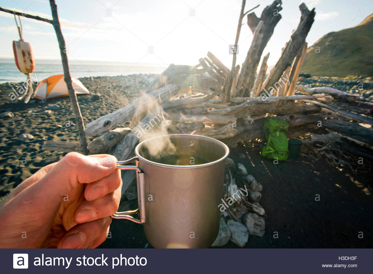 A steaming cup of coffee is seen in a campers hand. - Stock Image