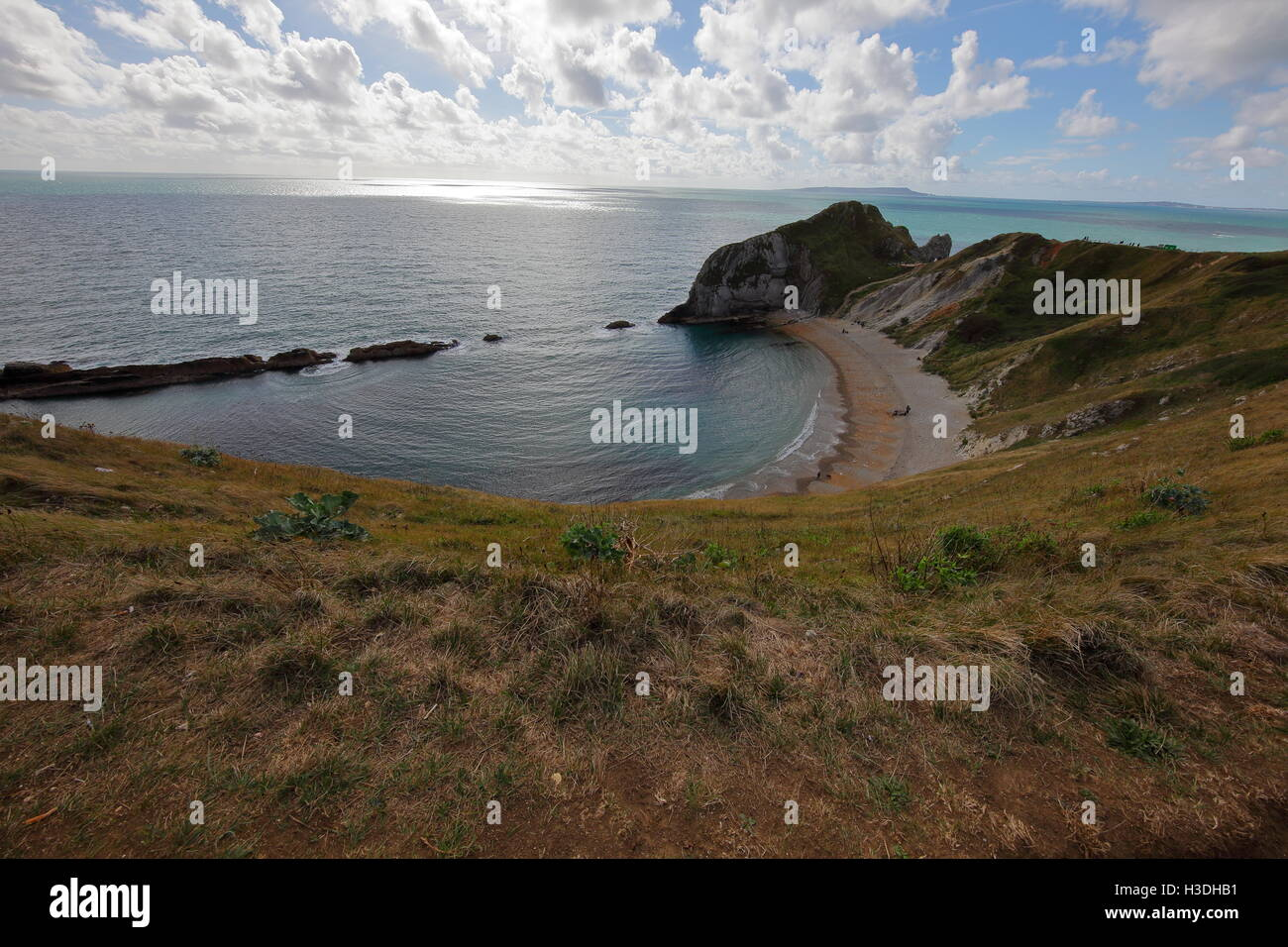 Looking towards a large rock outcrop on one end of a natural bay formed in the soft chalk with a shingle beach on - Stock Image