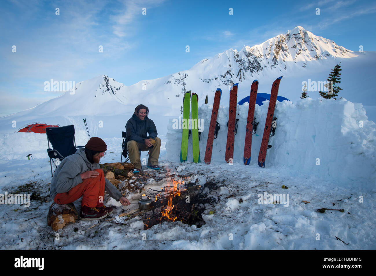 Snowboarders hanging out around a fire during sunset at base camp - Stock Image