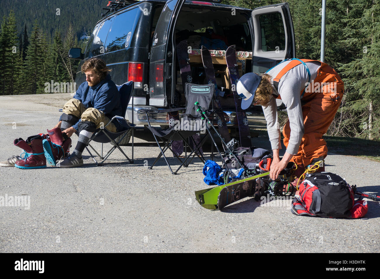Backcountry snowboarders gearing up on the side of the road - Stock Image