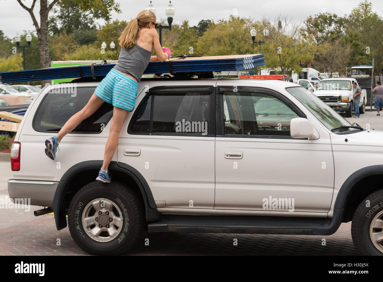 Charleston, South Carolina. 5th October, 2016. A woman ties down sheets of plywood on her SUV at a home store in - Stock Image