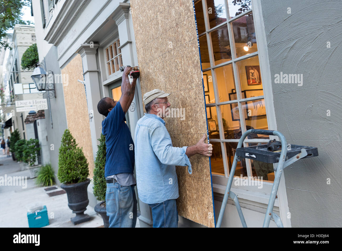 Charleston, South Carolina. 5th October, 2016. Workers board up the windows of an art gallery along Church Street - Stock Image