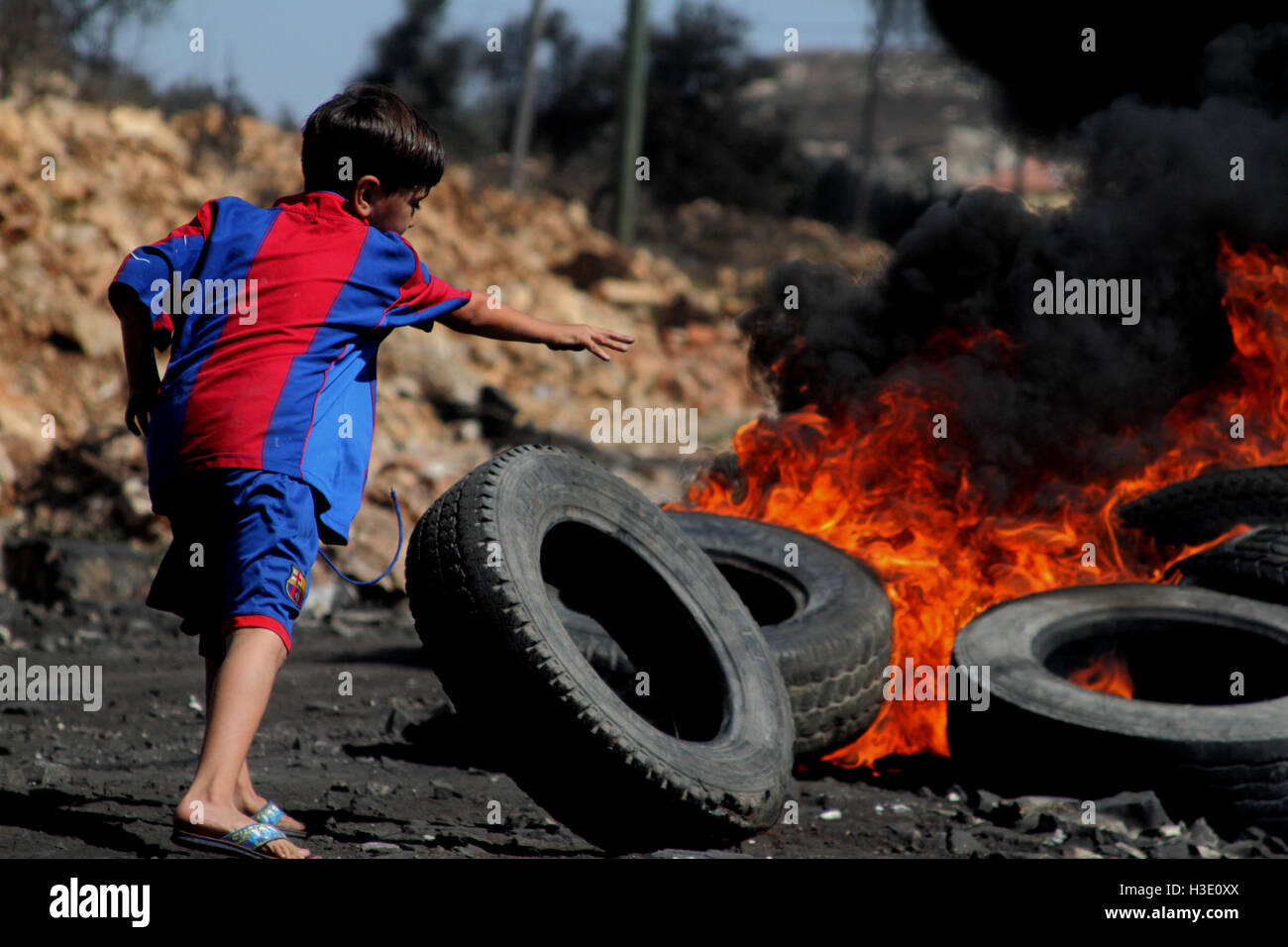 Nablus, West Bank, Palestine. 7th Oct, 2016. A Palestinian boy burns tires during clashes with Israeli security - Stock Image