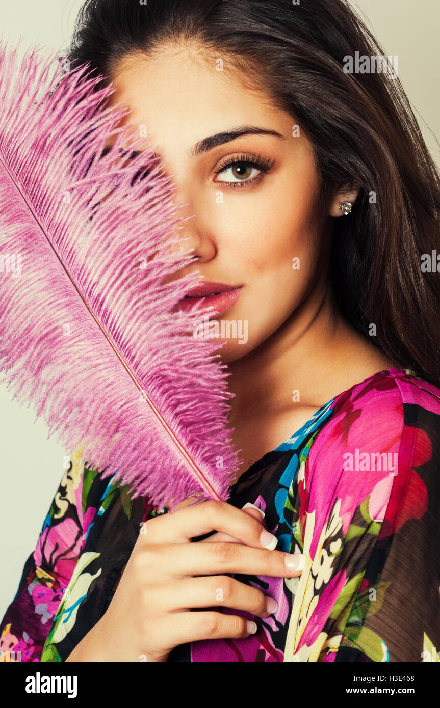 Beautiful young woman hiding face with pink feather - Stock Image