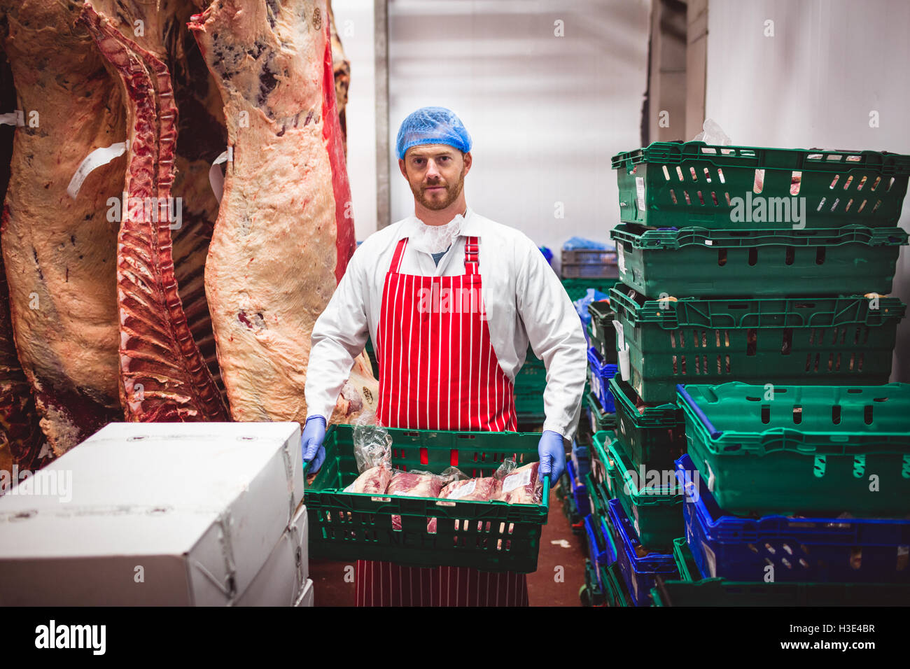 Portrait of butcher carrying a crate of red meat in storage room Stock Photo