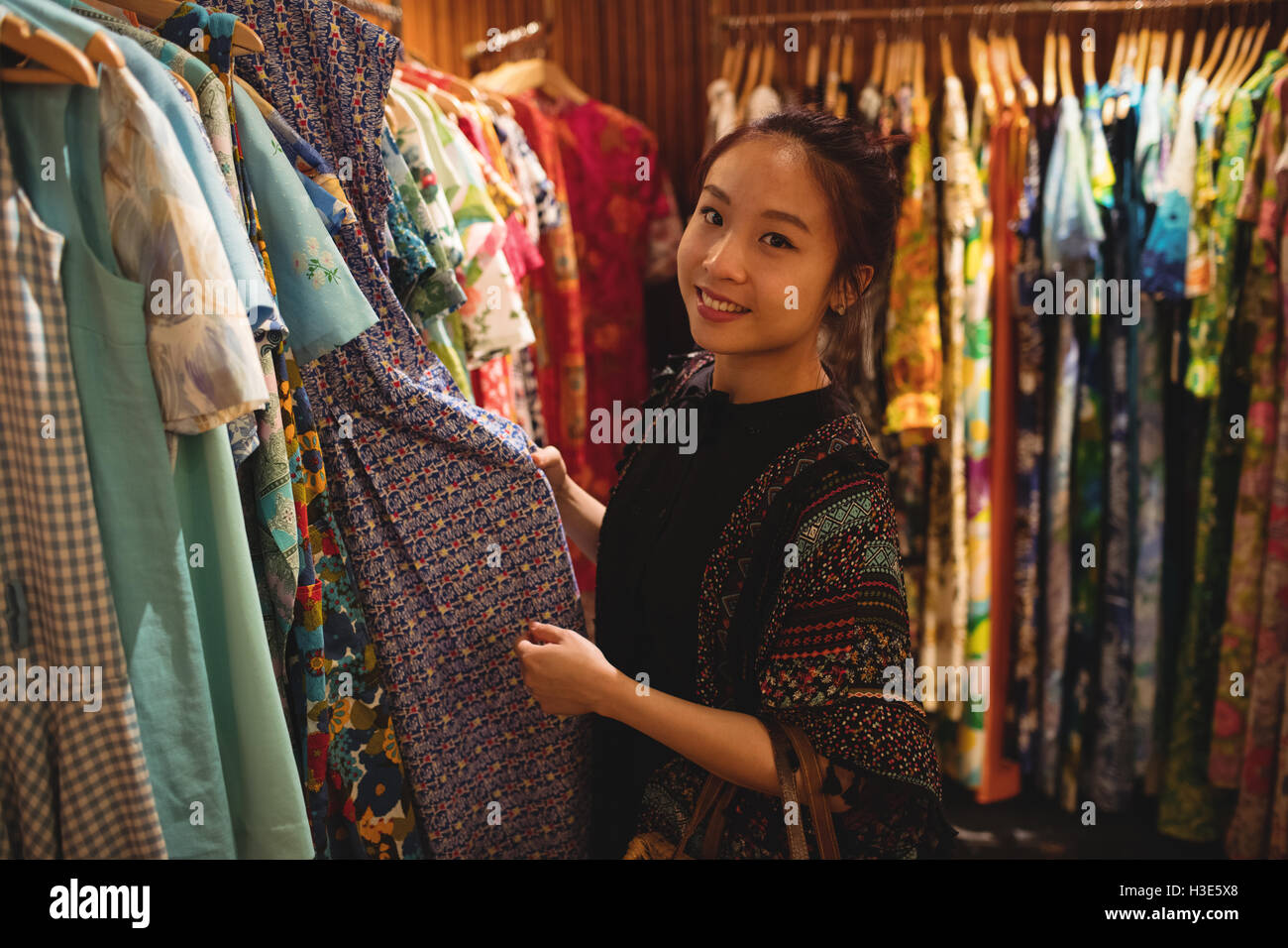 Portrait of smiling woman selecting a clothes - Stock Image