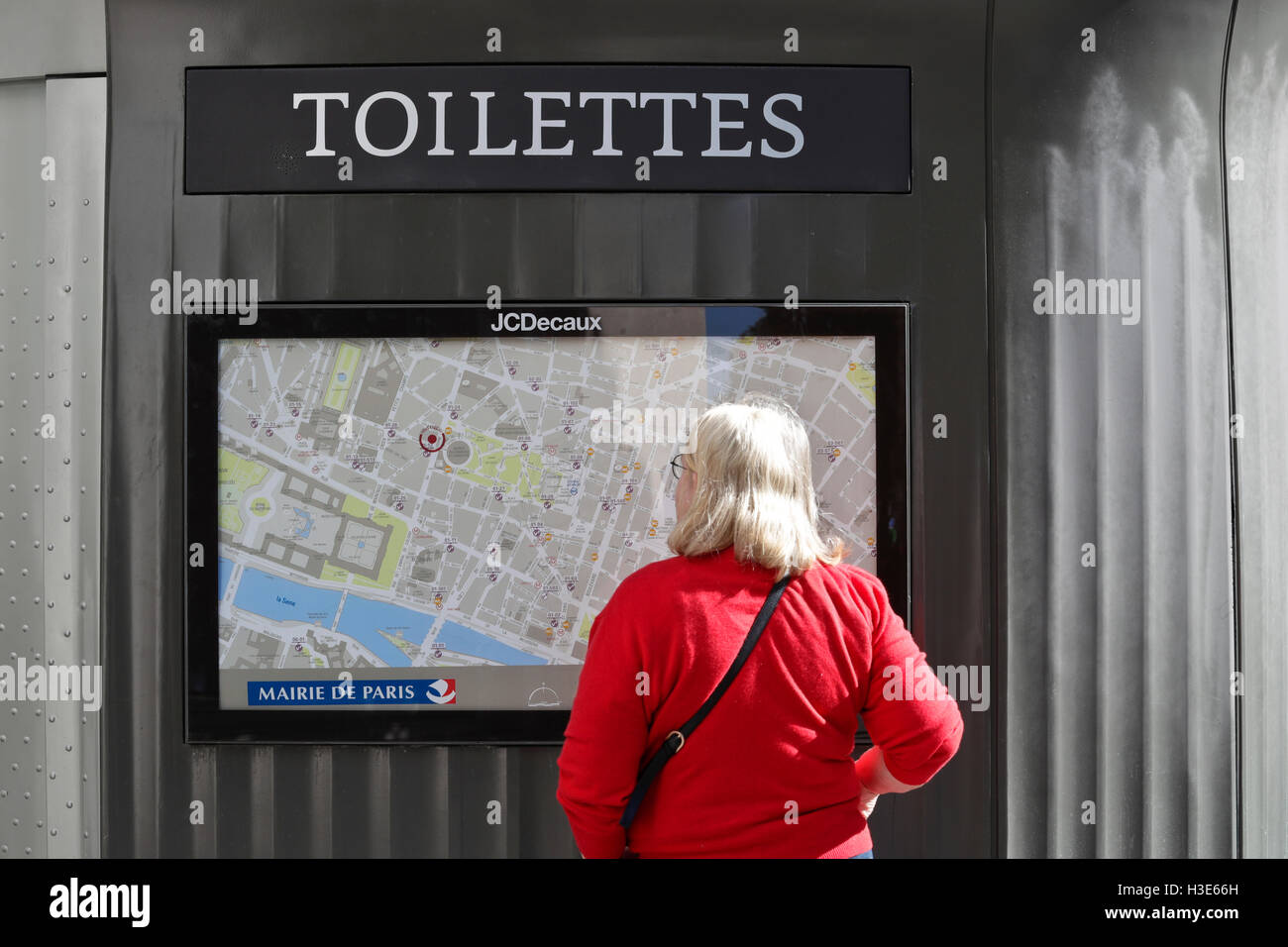 Tourist looking at a map of the city outdoors of a public toilette, in Paris. France - Stock Image