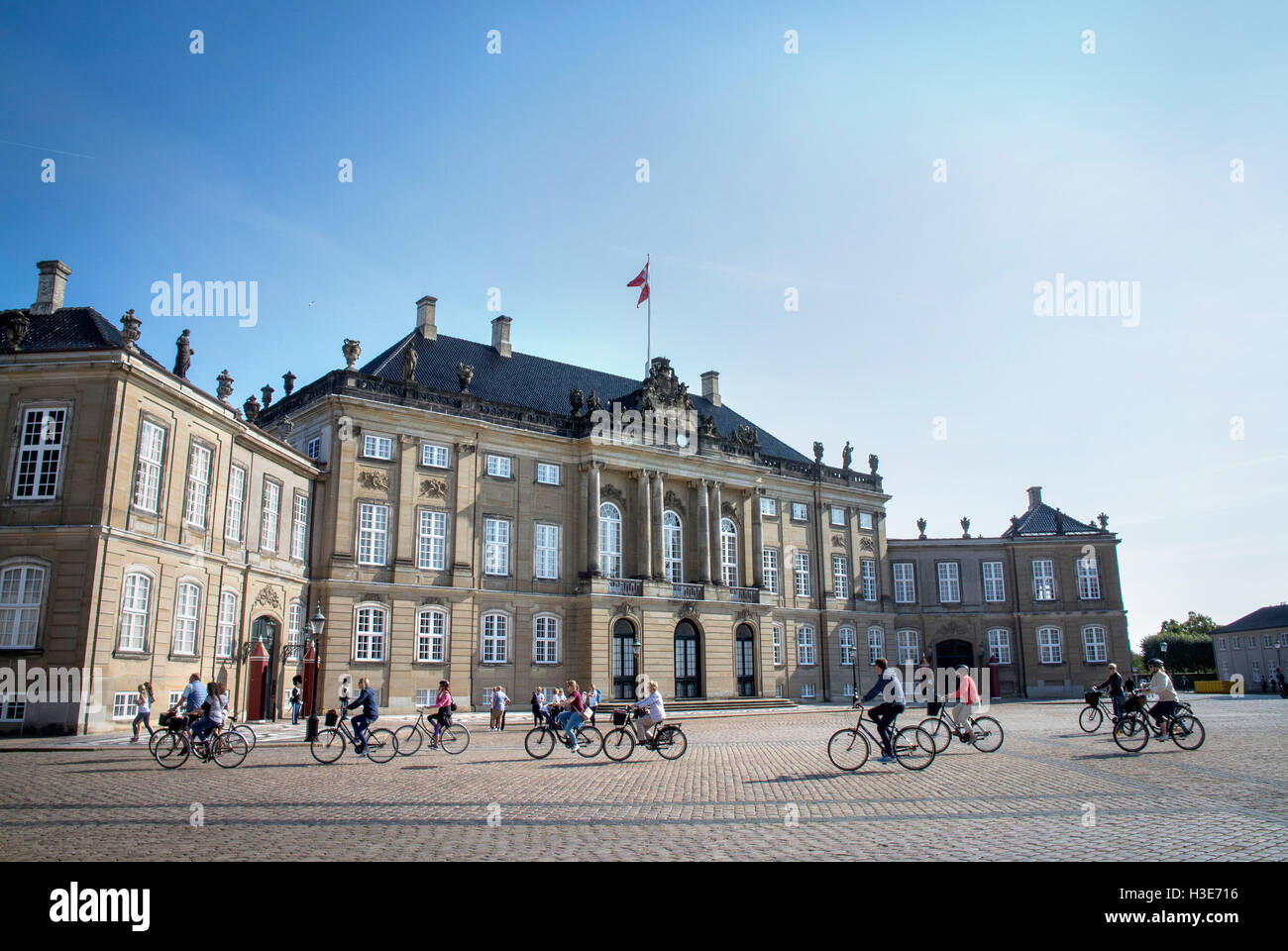 Cyclists pass in front of one of the buildings of the Amalienborg Palace the official residence of the Danish Royal's, - Stock Image