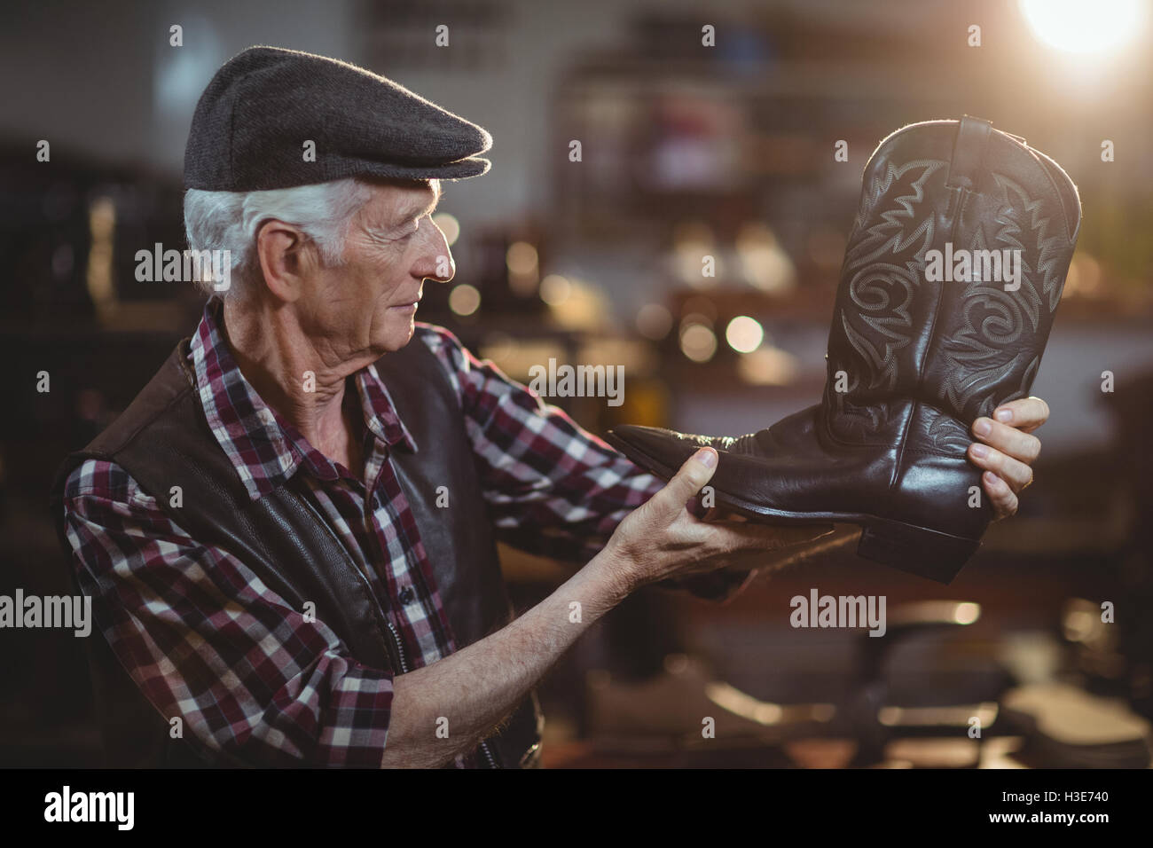 Shoemaker examining a shoe - Stock Image