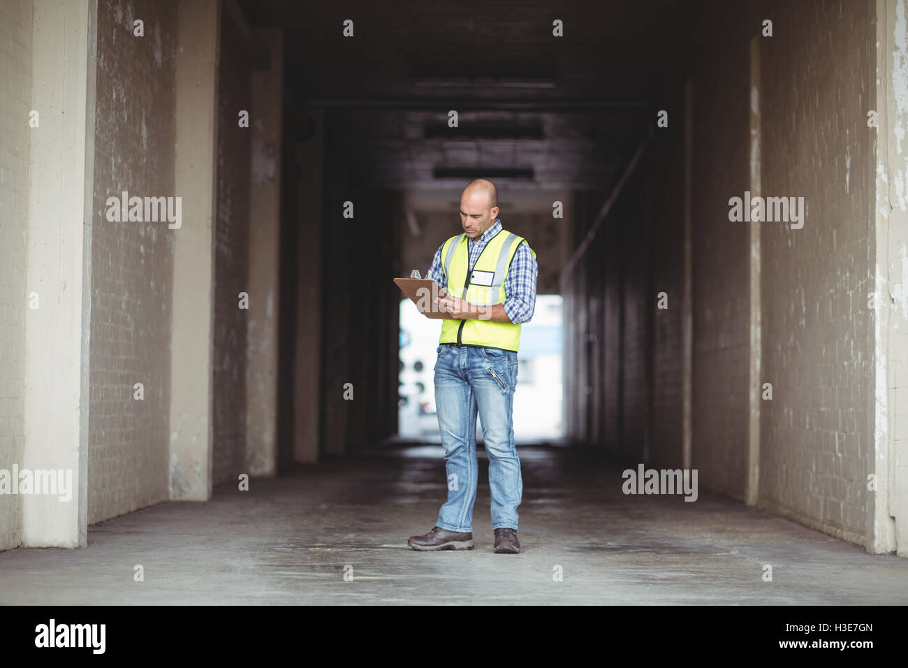 Construction worker writing on a clipboard - Stock Image