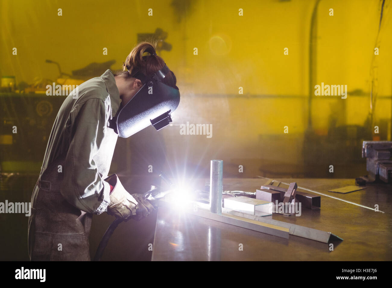 Female welder working on a piece of metal Stock Photo