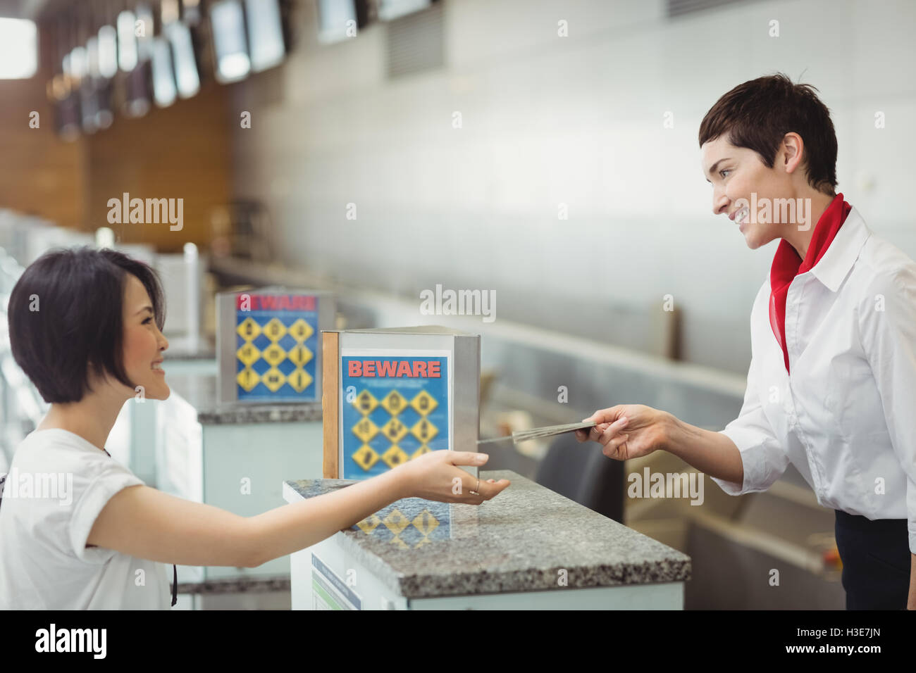 Airline check-in attendant handing passport to passenger - Stock Image