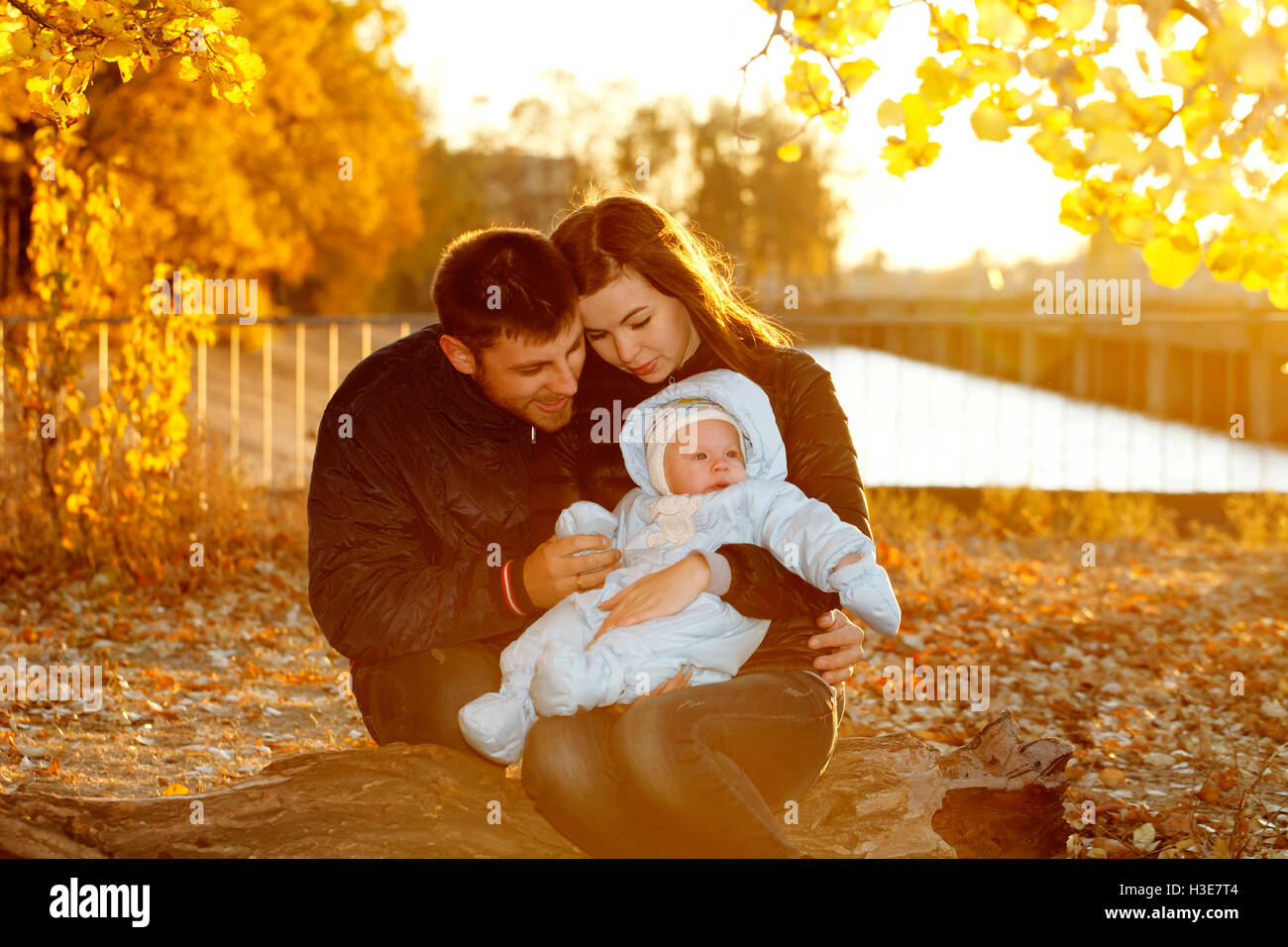 happy family walking outdoors, father, mother and cute baby