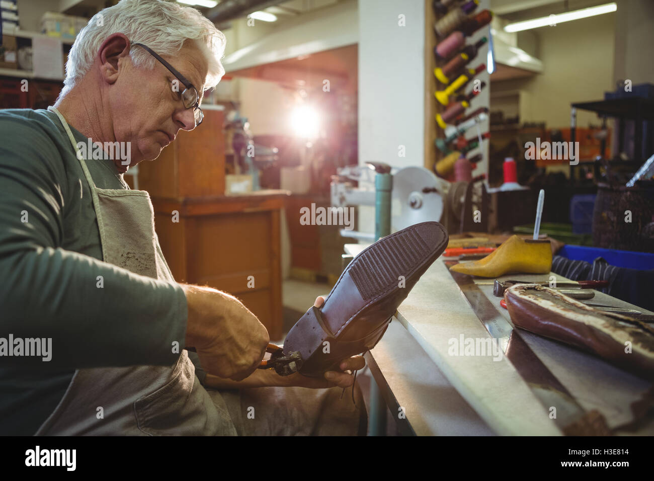 Shoemaker repairing a shoe - Stock Image