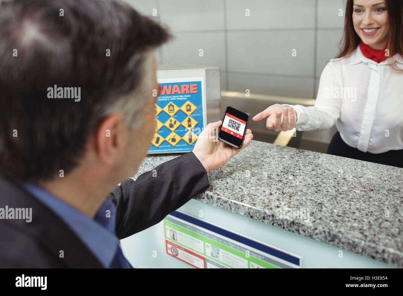 fdcdffb02a1 Businessman showing mobile boarding pass to airline check-in attendant -  Stock Image