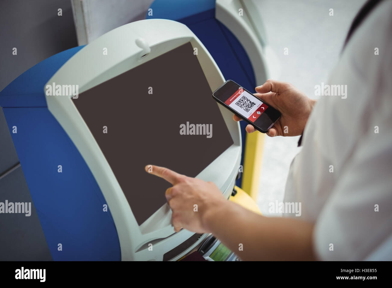 Traveller using self service check-in machine - Stock Image