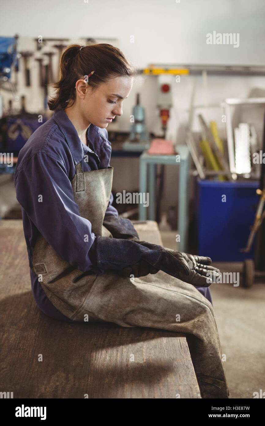 Female welder wearing glove - Stock Image