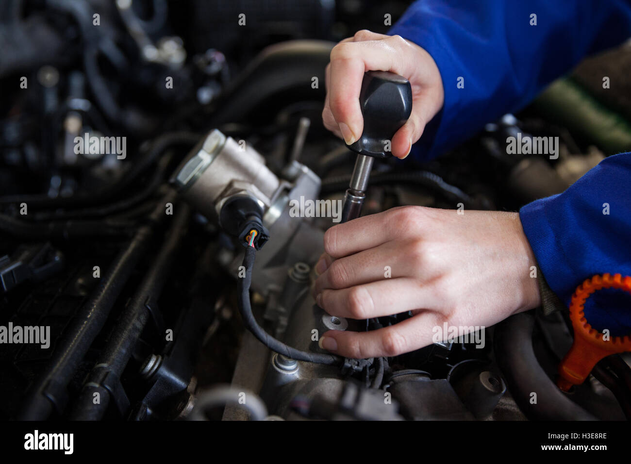Mechanic servicing car engine - Stock Image