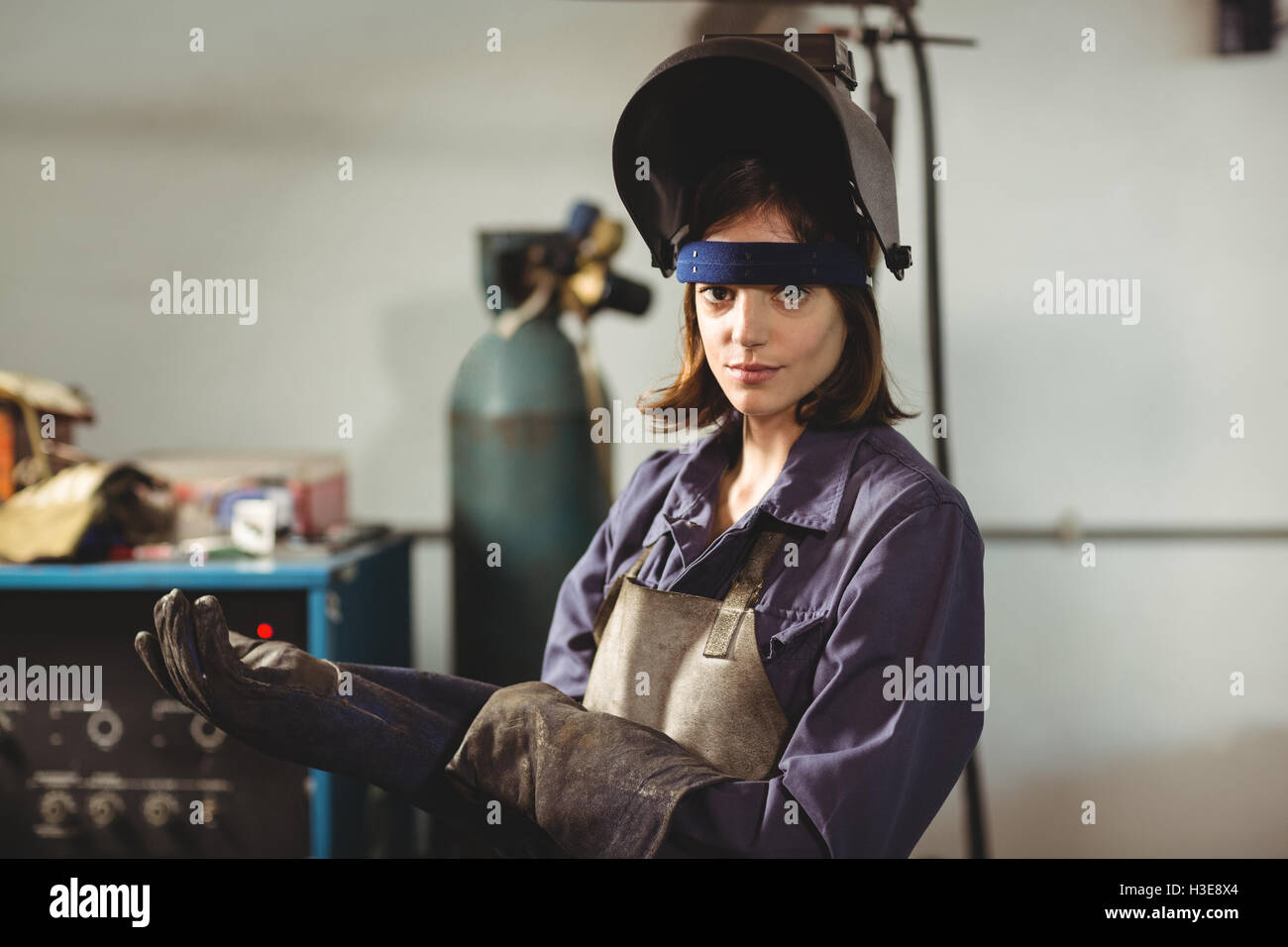 Portrait of female welder wearing glove - Stock Image
