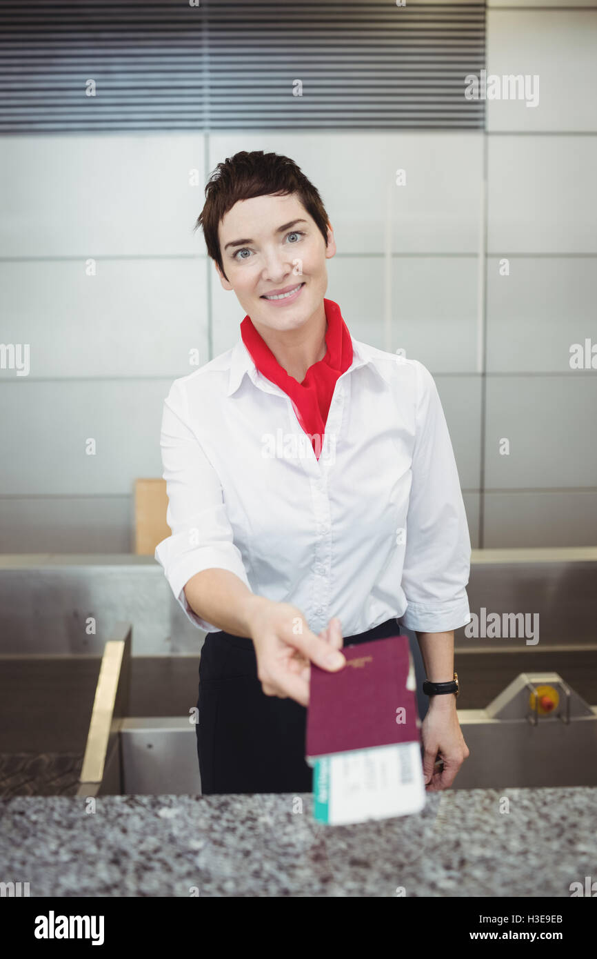 Airline check-in attendant giving passport to passenger - Stock Image