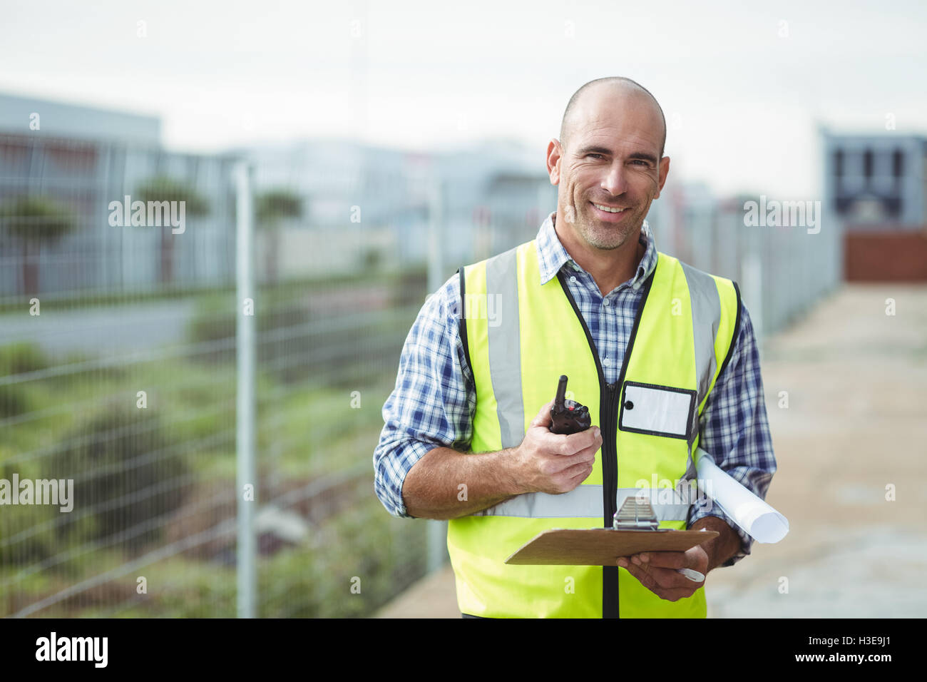 Construction worker holding walkie-talkie and clipboard - Stock Image