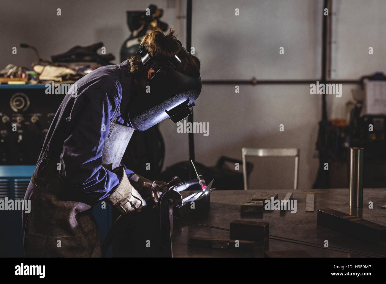 Female welder working on a piece of metal - Stock Image