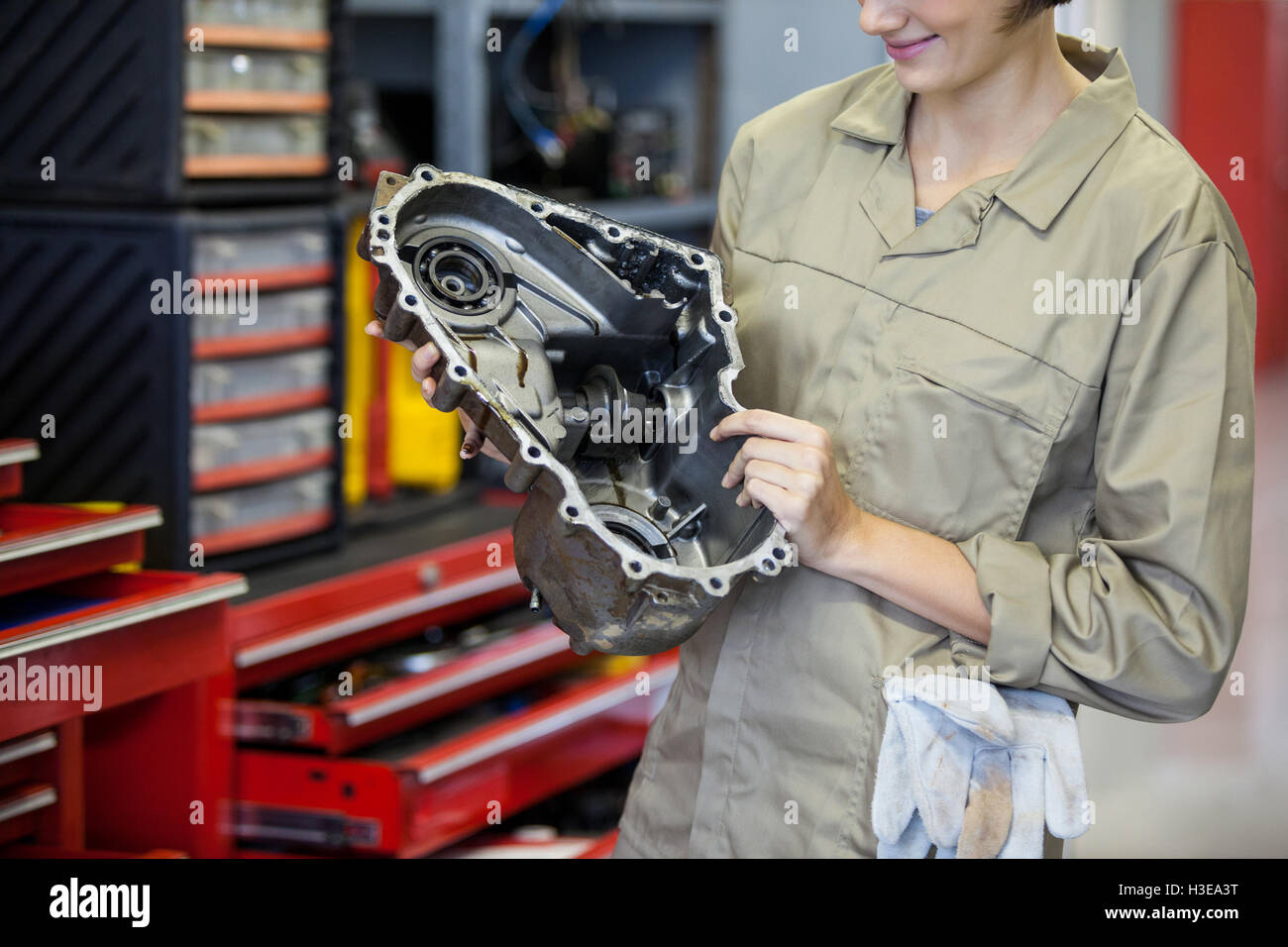 Female mechanic holding spare parts - Stock Image