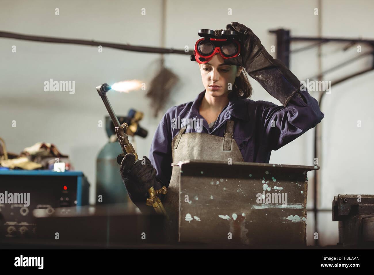 Female welder holding welding torch - Stock Image